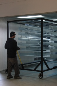 employee spraying frame of poly carbonate door
