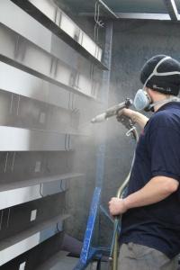employee spraying frame of poly carbonate door